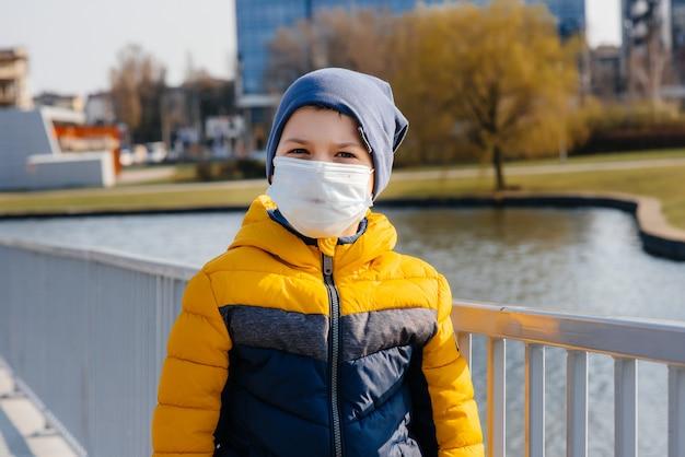 Un garçon se tient sur un fond gris dans un masque pendant une quarantaine avec de l'espace libre. quarantaine au masque