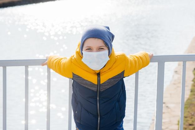 Un garçon se tient sur un fond gris dans un masque pendant une quarantaine avec de l'espace libre. quarantaine dans le masque.