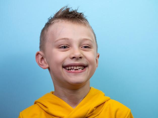 Un garçon de sept ans vêtu d'un sweat à capuche jaune pose devant une caméra sur fond bleu