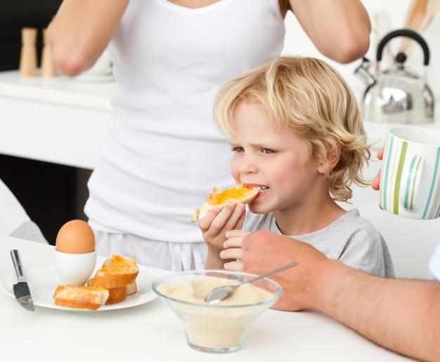 Garçon sérieux manger un toast avec de la marmelade au petit déjeuner