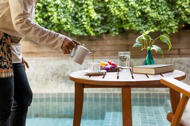 Garçon servant du café et des fruits frais sur une table en bois dans la chambre d'hôtel.