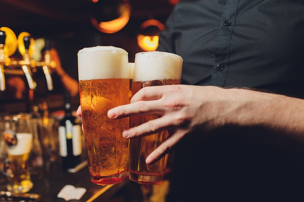 Garçon servant des verres de bière froide sur le plateau