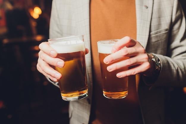 Garçon servant des verres de bière froide sur le plateau.