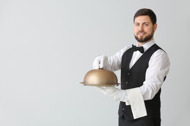 Garçon de sexe masculin avec plateau et cloche sur fond gris