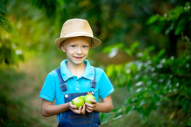 Un garçon de six ans se dresse dans une robe bleue et un chapeau dans un jardin avec des pommiers