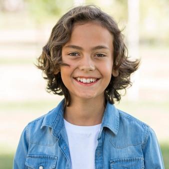 Garçon smiley posant dans le parc