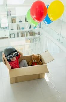 Garçon avec son ours volant dans une boîte avec des ballons