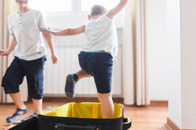 Garçon sortant des bagages à la maison