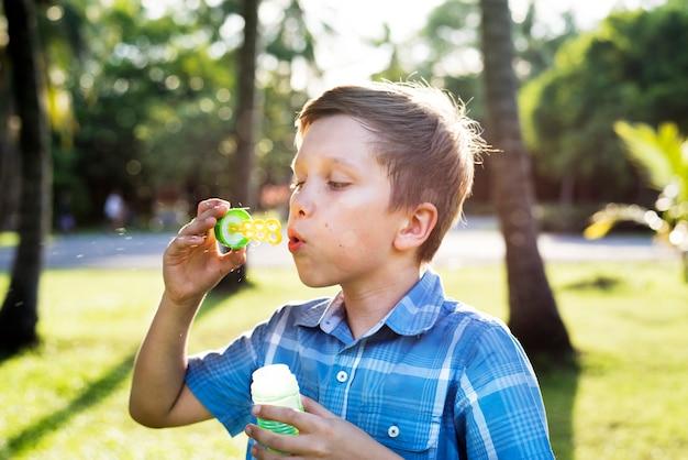 Garçon soufflant des bulles de savon dans le parc