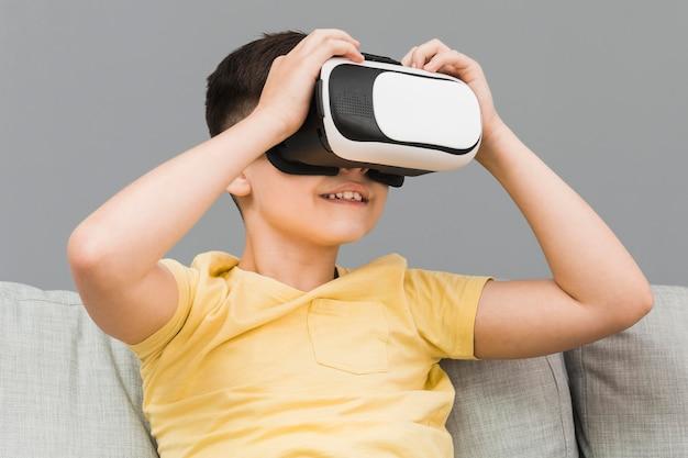 Garçon souriant à l'aide d'un casque de réalité virtuelle