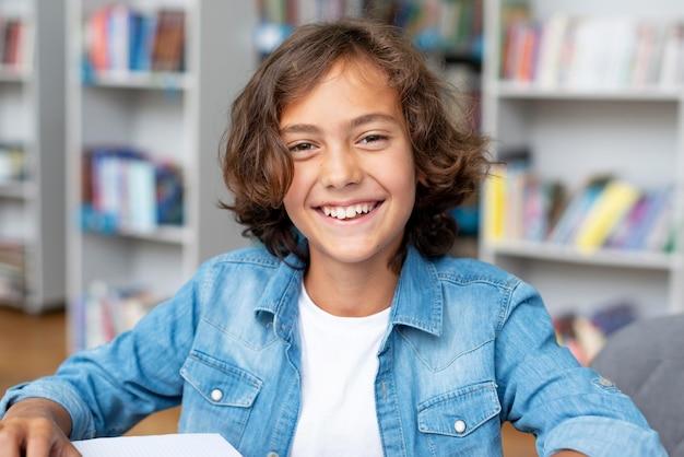 Garçon souriant alors qu'il était assis dans la bibliothèque