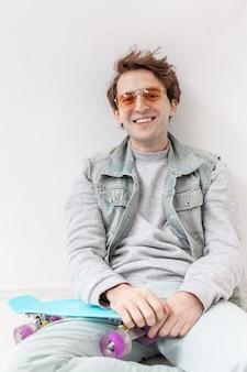 Garçon souriant assis avec planche à roulettes à côté