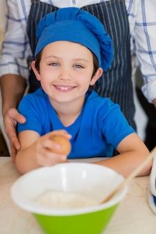 Garçon souriant au chapeau de chefs tenant l'oeuf dans la cuisine