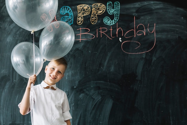 Garçon souriant avec des ballons près de joyeux anniversaire écrit