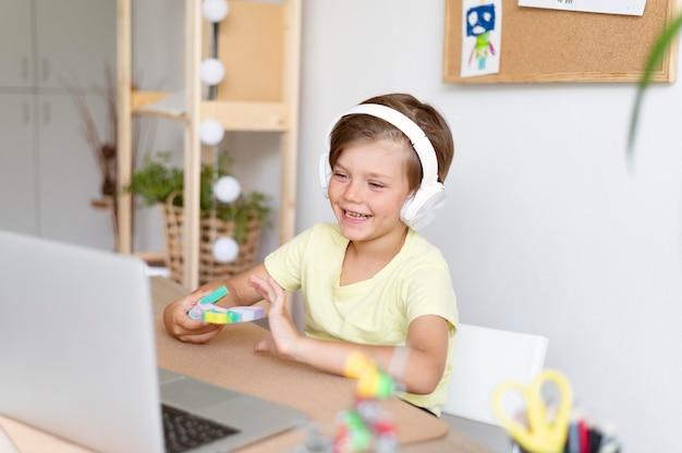Garçon souriant de coup moyen portant des écouteurs