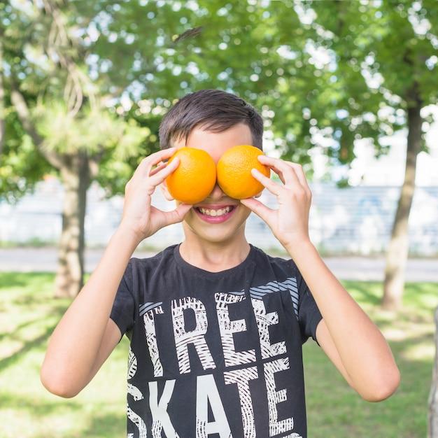Garçon souriant couvrant ses yeux avec des oranges entières fraîches dans le parc