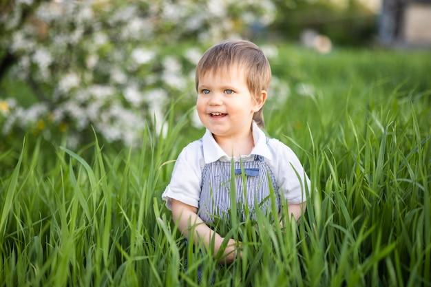 Garçon souriant drôle en salopette bleu denim et yeux bleus vifs. c'est amusant de se cacher dans les hautes herbes vertes d'un jardin printanier chaud sur fond d'arbres en fleurs.