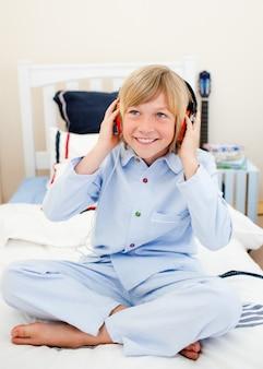 Garçon souriant écoute de la musique assis sur le lit