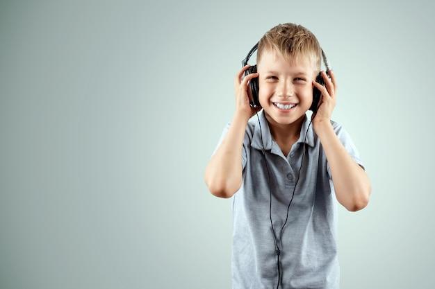 Garçon souriant écoute de la musique dans les gros écouteurs isolé sur fond blanc