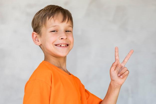 Garçon souriant en faisant le signe de la paix