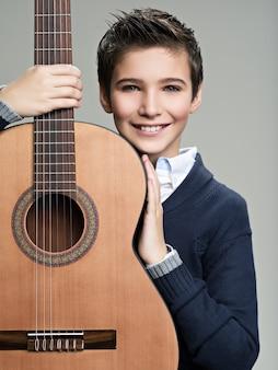 Garçon souriant avec guitare.