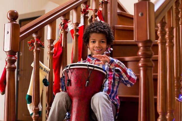 Garçon souriant jouant sur tambour jeune mulâtre gai avec tambour laisse ici quelques talents de musique traditionnelle...