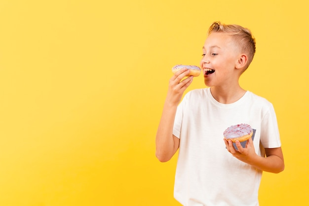 Garçon souriant mange un délicieux beignet