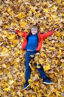 Garçon souriant se trouve dans les feuilles d'automne jaunes. vue de dessus. concept d'automne
