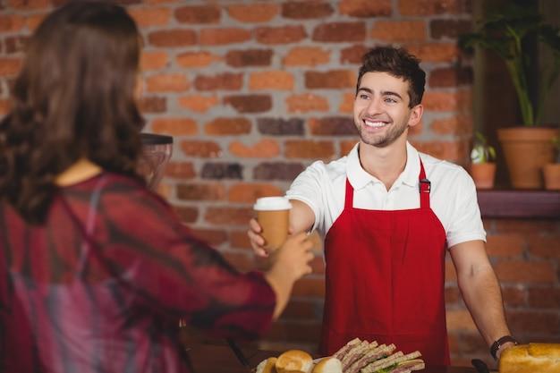 Garçon souriant servant un café à un client