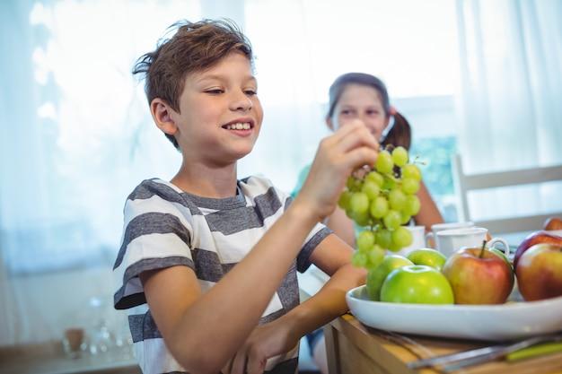 Garçon souriant tenant une grappe de raisin