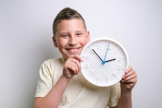 Garçon souriant et tenant le programme d'alarme d'horloge et le concept de synchronisation