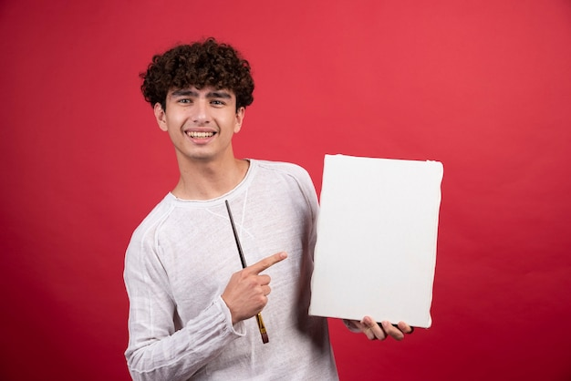 Garçon souriant tenant une toile vide et un pinceau