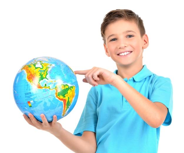Garçon souriant en tenue décontractée globe en mains isolé sur blanc