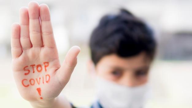 Garçon avec stop coronavirus message à portée de main