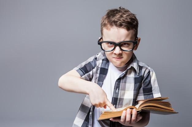 Garçon strict dans des verres avec livre en mains, séance photo en studio. concept d'éducation scolaire
