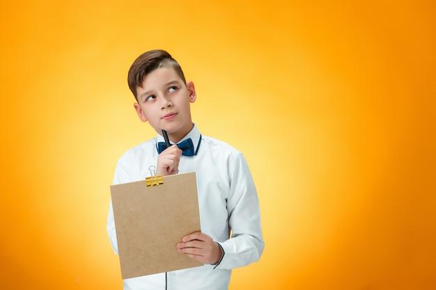 Le garçon avec stylo et tablette pour notes