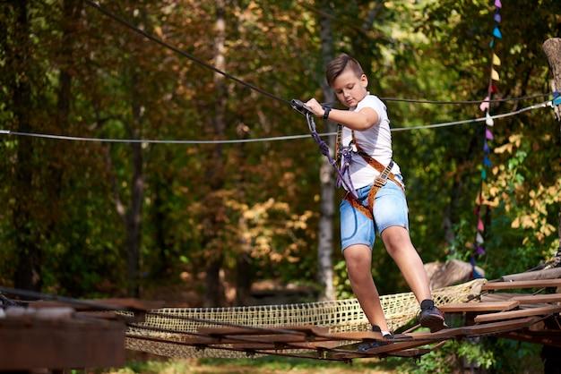 Le garçon surmonte l'obstacle dans le parc à cordes.