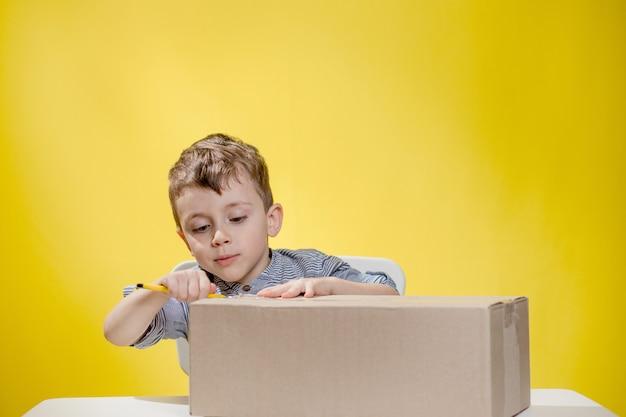 Garçon surpris regardant ouvrir une boîte et haletant de surprise en voyant le contenu de la boîte tout en enregistrant un vlog de déballage