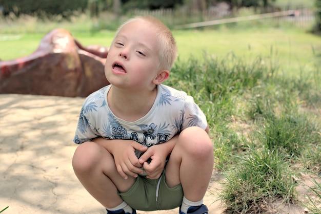 Garçon avec le syndrome de down pose pour un portrait en plein air