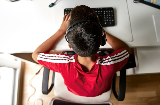 Garçon avec t-shirt rouge dans l'ordinateur