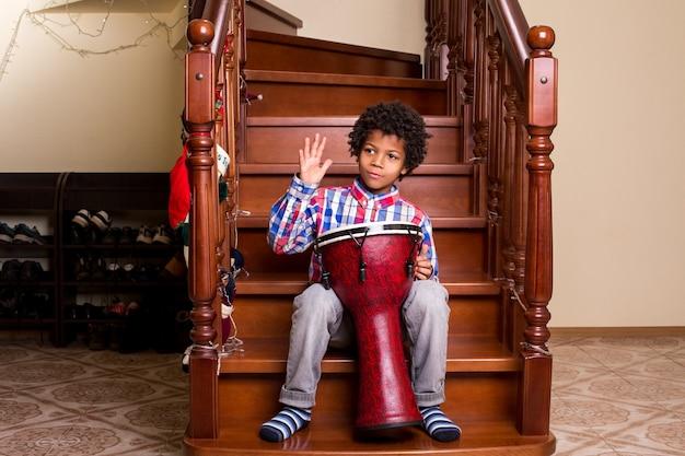 Garçon avec tambour dans les escaliers performance de tambour de noël pour garçons afro que diriez-vous de quelques chansons de vacances moment de ...