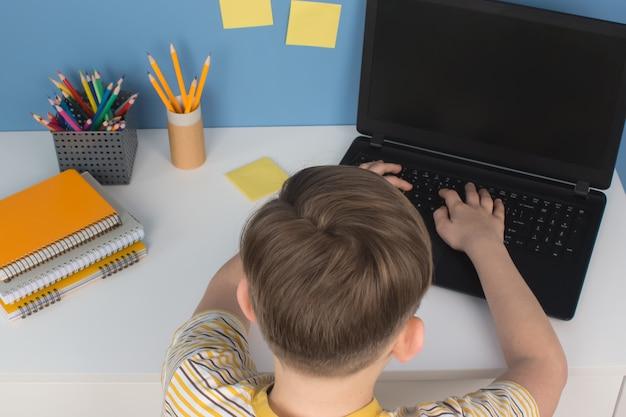 Garçon tapant sur un ordinateur portable tout en faisant ses devoirs