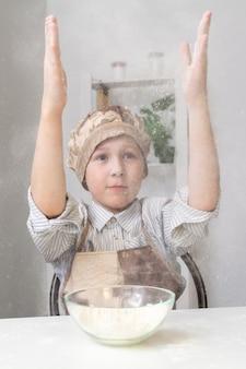 Garçon tape dans ses mains avec de la farine, un nuage de farine se lève