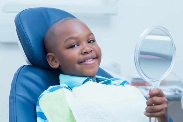 Garçon tenant au miroir dans la chaise des dentistes