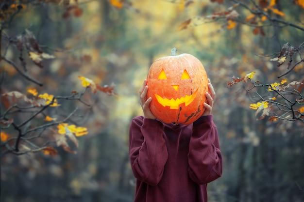 Garçon tenant citrouille sculptée pour halloween devant sa tête dans la sombre forêt d'automne.