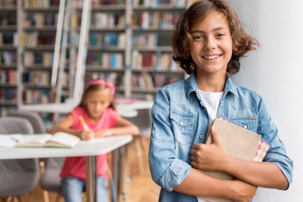 Garçon tenant des livres dans la bibliothèque à côté de son collègue