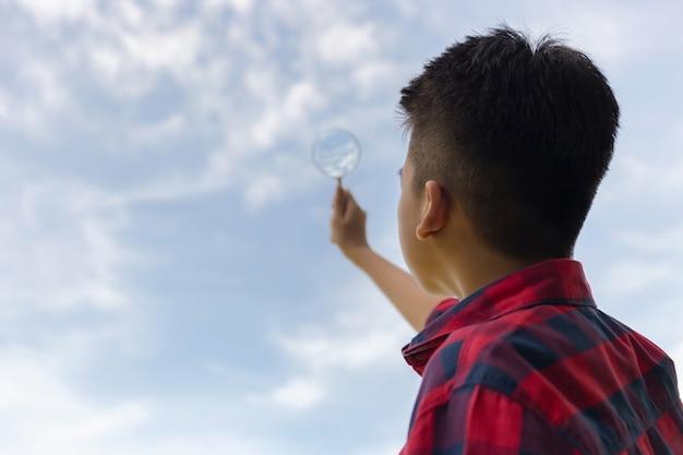 Garçon tenant une loupe et regardant vers le ciel
