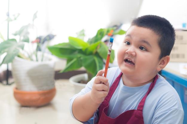 Un garçon tenant un pinceau dans la maison est une nouvelle ère d'apprentissage et de détention.