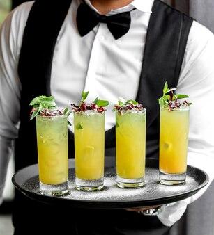 Garçon tenant un plateau avec des verres de mojitos au citron garnis de menthe et de roses séchées