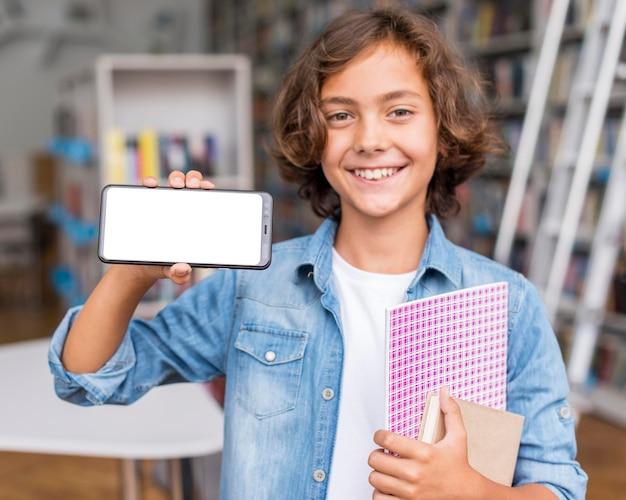 Garçon tenant un téléphone à écran vide dans la bibliothèque
